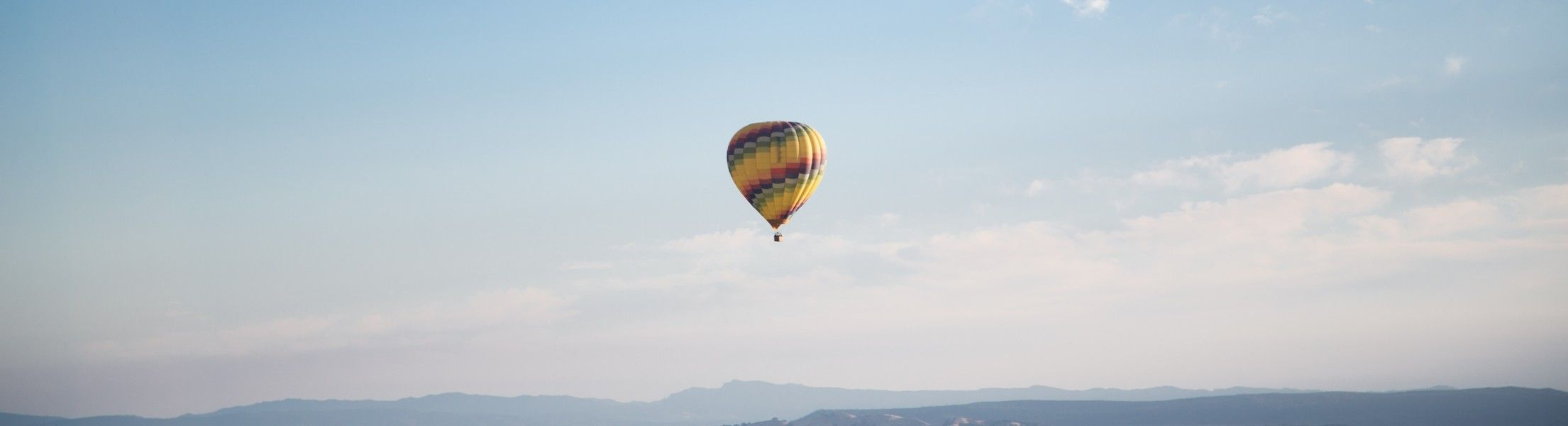 Heißluftballon in der Lut bei blauem Himmel