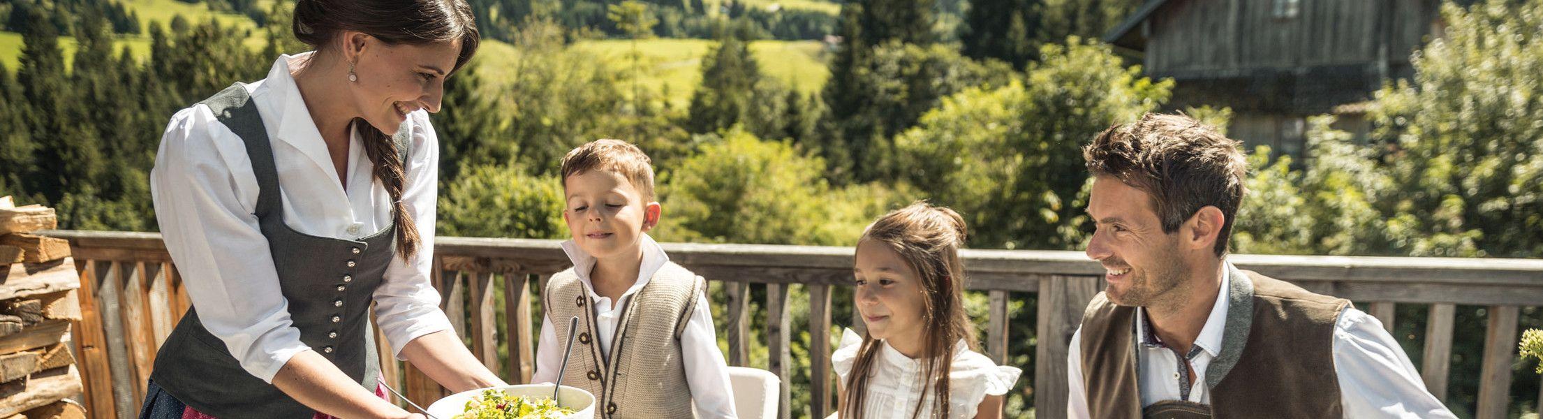 Familie am Tisch auf der Terrasse der Luxuslodge