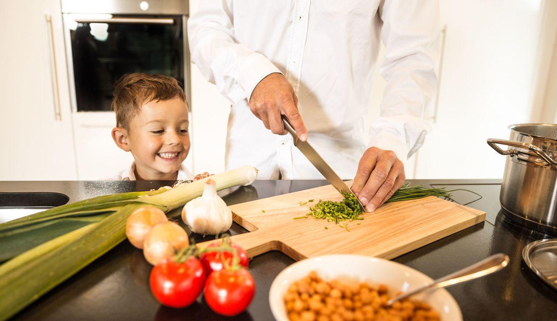 Junger Bub sieht beim Kochen zu