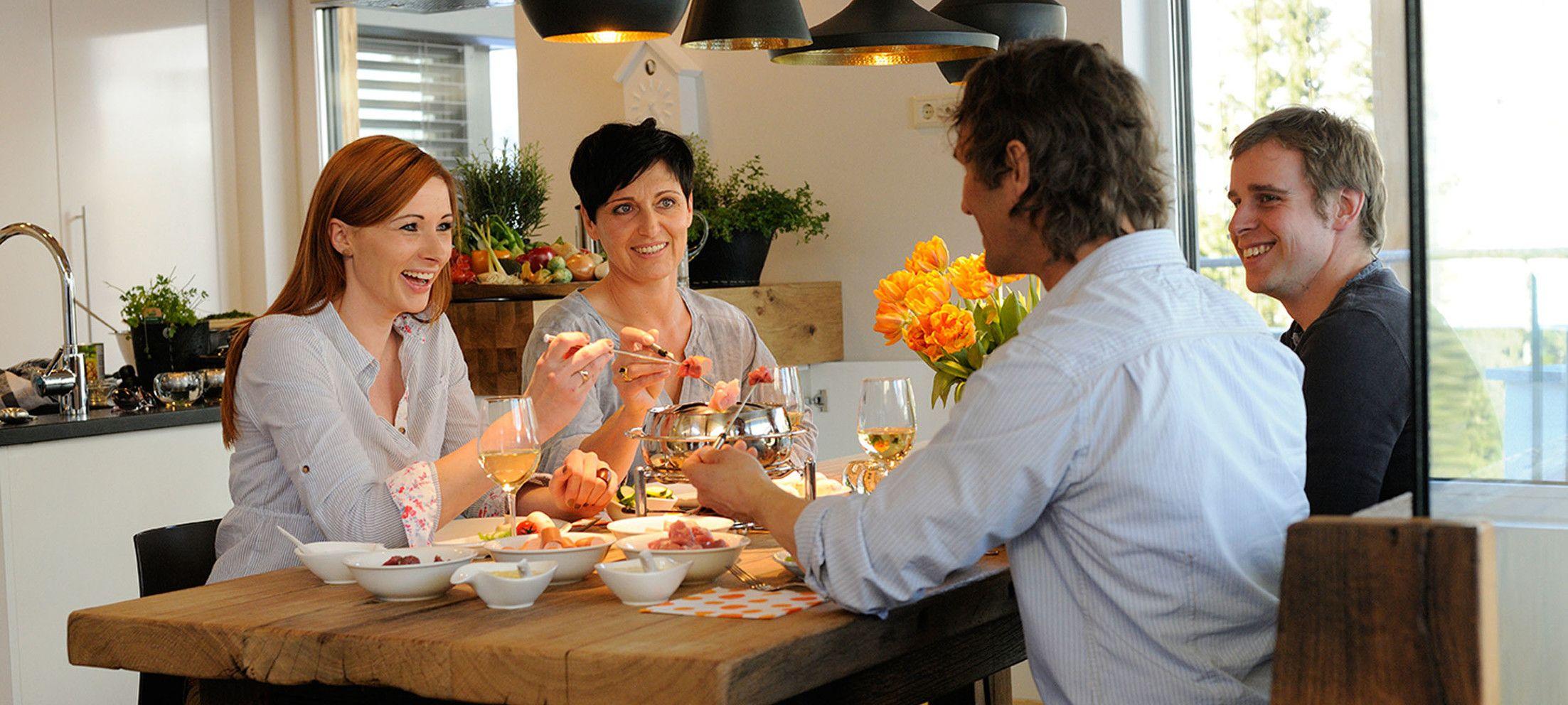 Vier Freunde essen Fondue in Luxuslodge