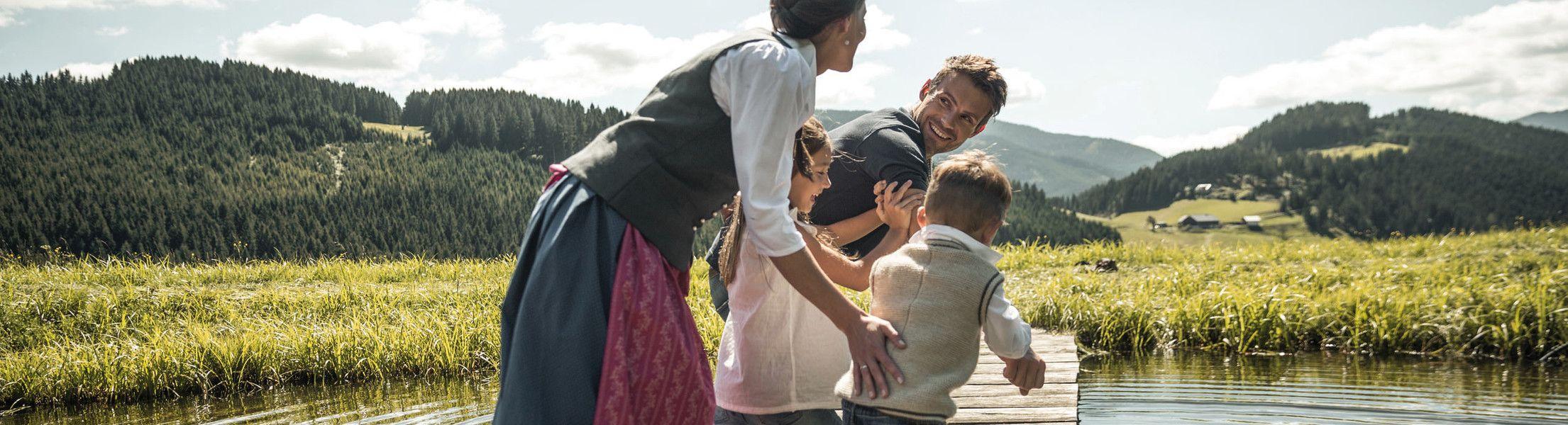 Familie rennt über Steg am auf See im Lammertal