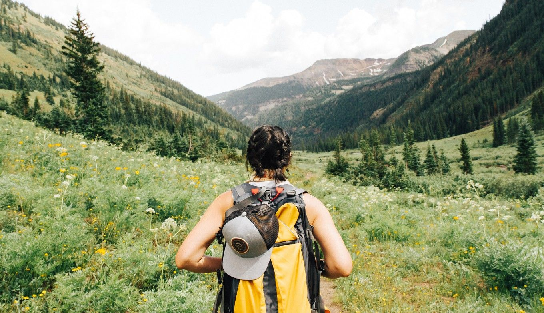 Frau wandert mit Rucksack in grüner Wiese