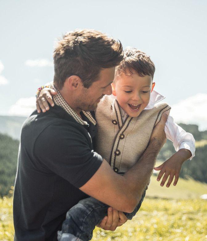 Vater mit Kind im Arm in einer Wiese