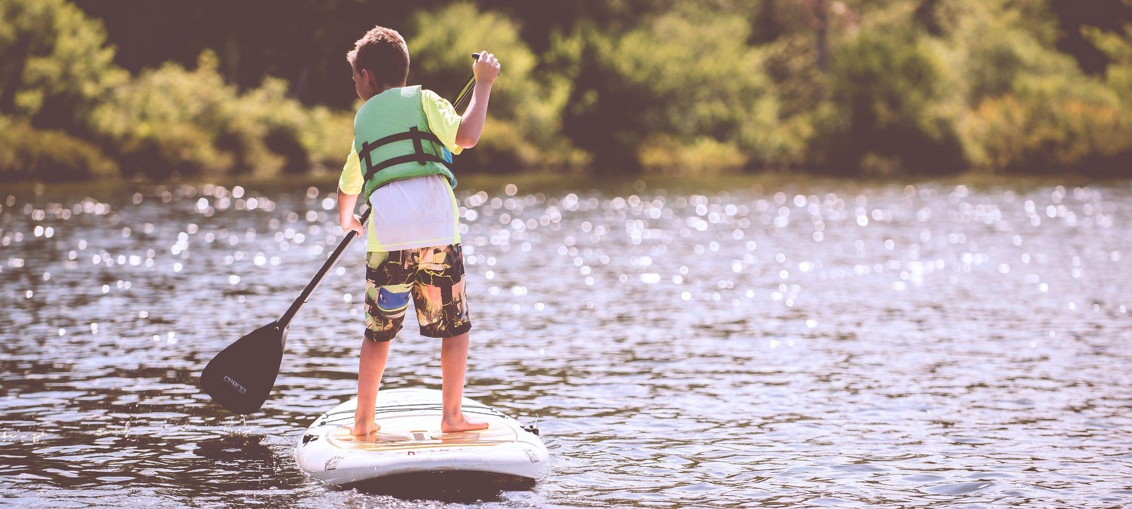 Kind steht auf Stand-Up Paddle im Wasser