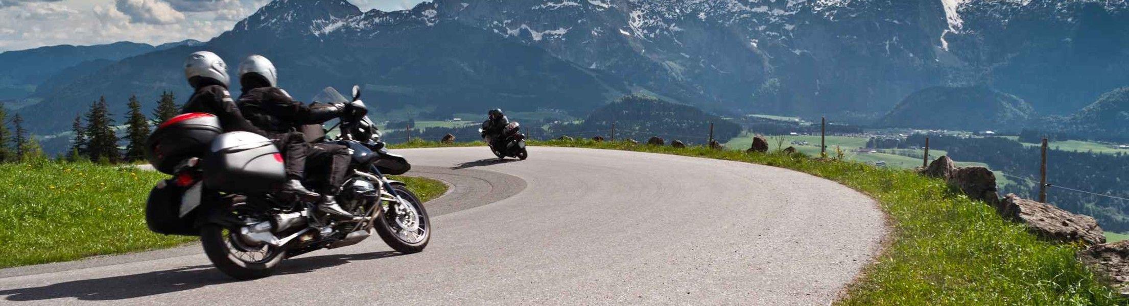Motorradfahrer in Kurve in den Alpen