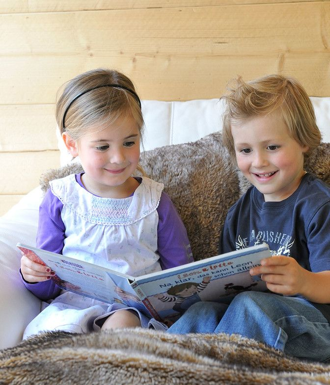 Kinder lesen Buch in Luxuslodge
